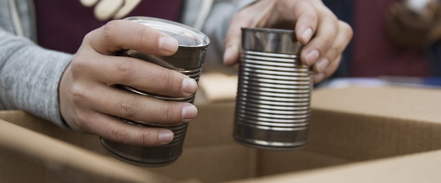 Volunteer packing tin cans into cardboard box