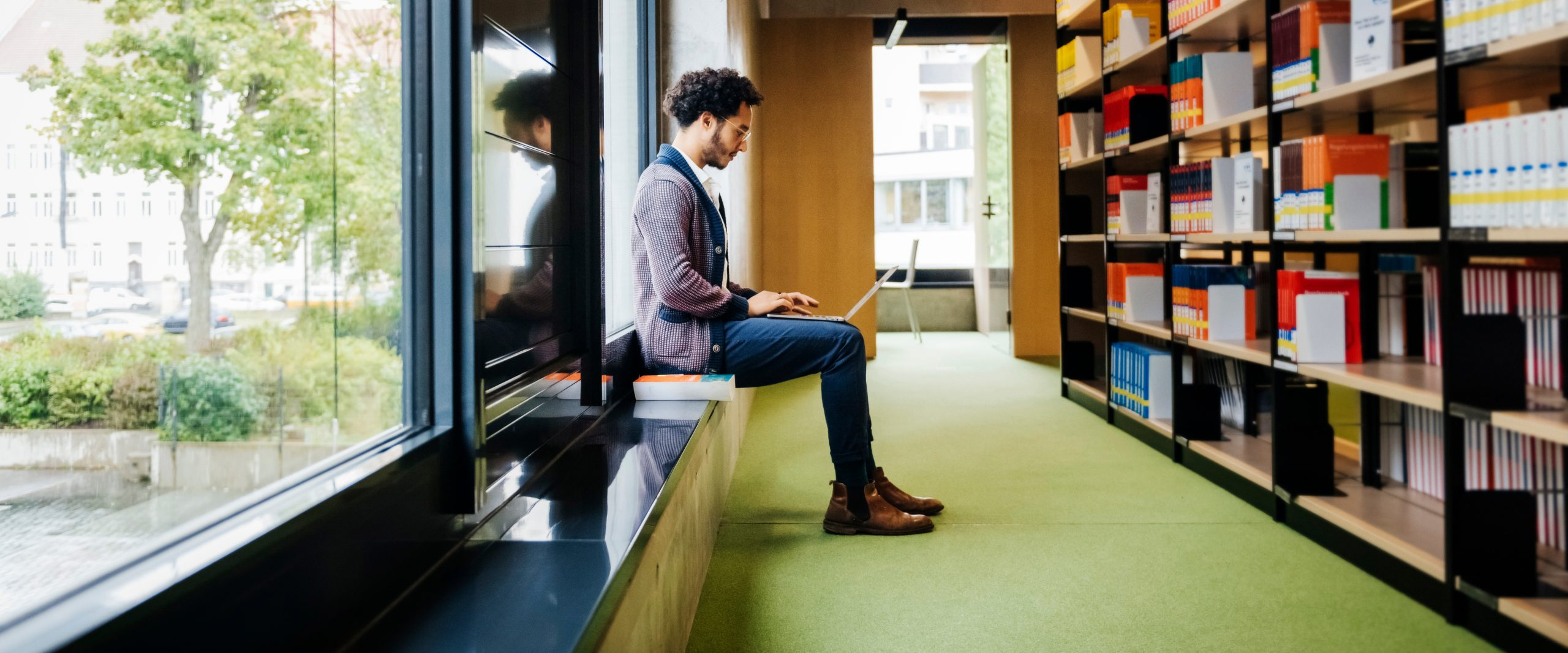 Man on laptop in a library