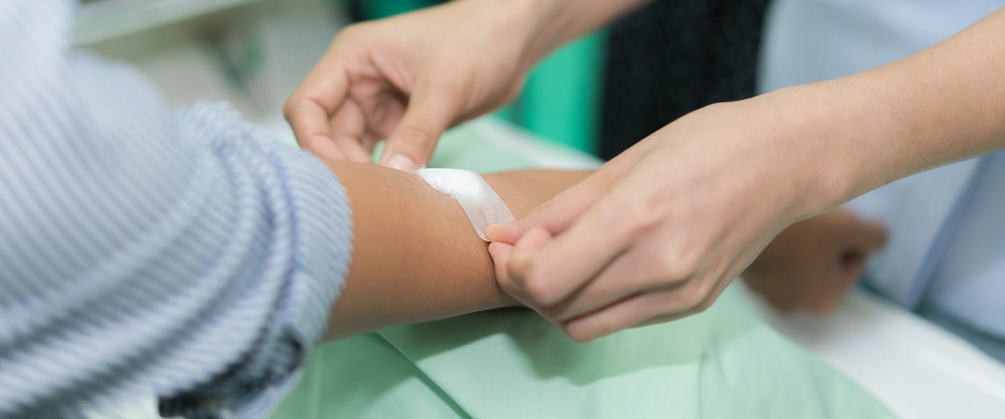 Nurse applying bandage on patient's hand after blood test in hospital.