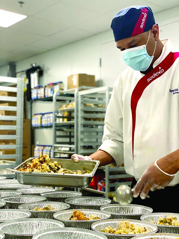 Sodexo employee preparing meals.