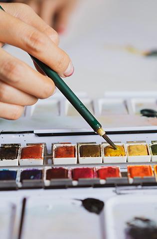 Illustrator painting at work desk, close-up