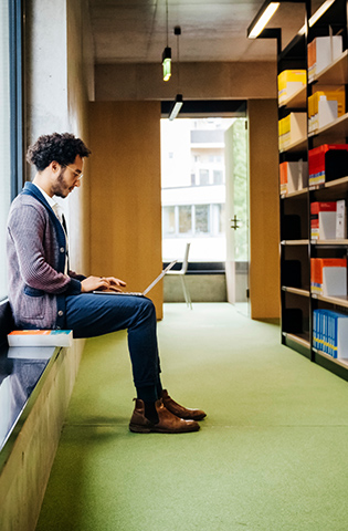 Man Sitting By Large Window Working In Library
