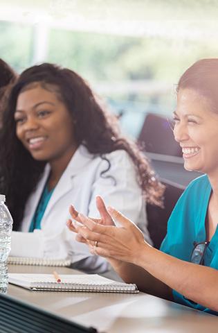 Female medical professionals applaud speaker during medical conference
